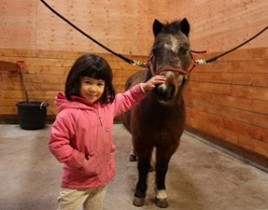 A pre-school riding student pets her pony.